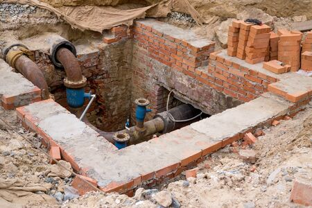 open trench: Pit with brick wall to repair underground sewer pipeline Stock Photo
