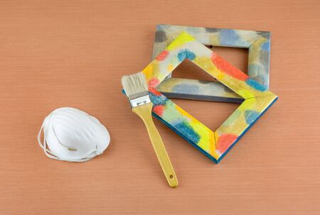 respirator: Wooden frame painted with colored paints, brush and respirator on wooden surface table