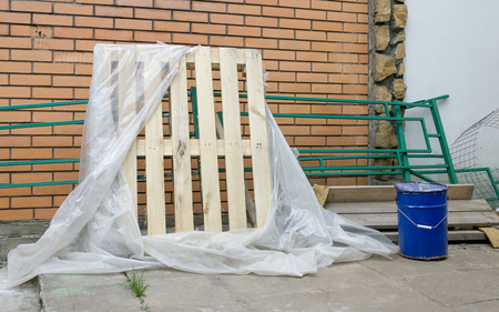 dismantling: New wooden pallet wrapped in cellophane near brick wall