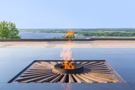 kudos: Burning eternal flame at mass tomb of soldiers on background of landscape with river. Blurred background
