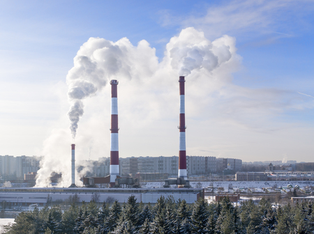 snowbound: Thermal power plant with smoking chimneys in background of city. In foreground snowbound forest Stock Photo