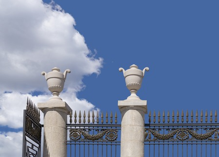 entrance gate: Metal fence with decorative plaster vases on background sky