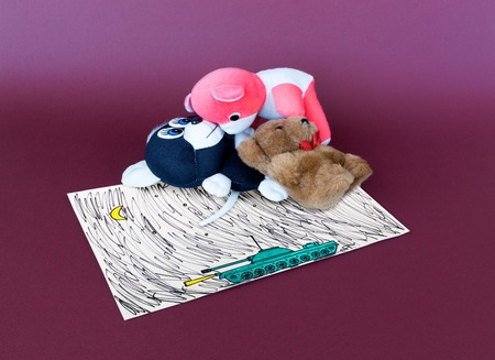 stuffed toys: Stuffed toys and picture of military tank on purple background