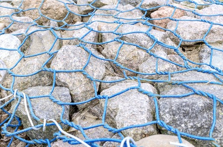 gabion mesh: Gabion-grey stones kepted with lattice made of blue wire.Closeup. Small depth of field.