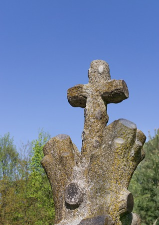 Stone cross in shape of tree on old Christian cemetery