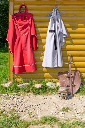 Knights cloak and dress hanging on wooden wall. Near on ground - shield, sword and helmet