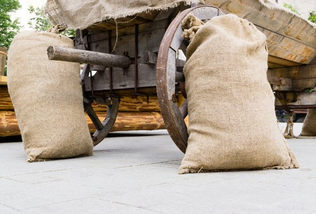 Closed filled jute bags standing near wheels of cart Stock Photo