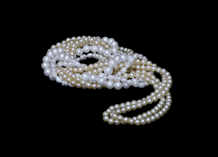 Twisted strings of river and sea pearls isolated on black background
