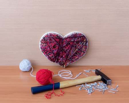 Panel of heart shaped of thread and nails, hammer and clews are on wooden table with copy space Stock Photo