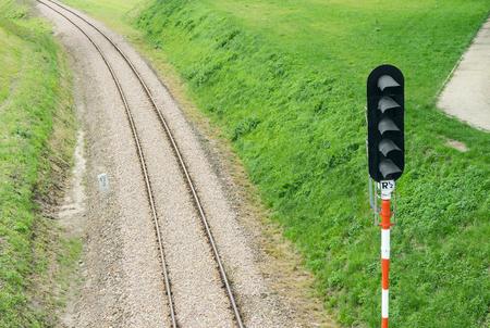 Rails of railroad tracks and semaphore are on railway embankment Imagens