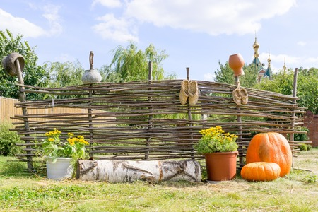 Orange pumpkins and yellow flowers near wicker fence on which hang bast shoes and clay pots Stock Photo