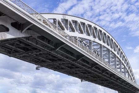 metal grate: Metal arch of railway bridge against sky with clouds