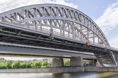 Metal arch of railway bridge above river against sky with clouds
