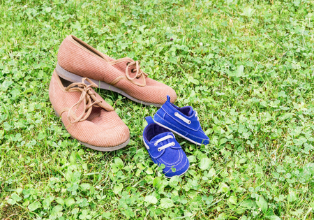 Mens corduroy sneakers and infant shoes are on lawn. Copy space Stock Photo