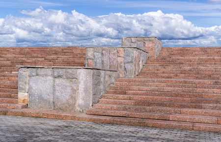 Red granite staircase with pedestals faced stone and sky with clouds