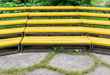 Empty wooden benches of yellow color are in outdoors theater Stock Photo
