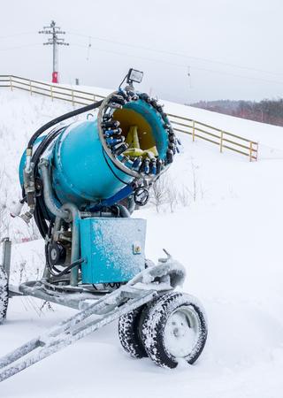 Old blue snow cannon is at standstill on ski slope