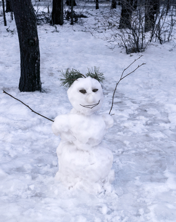 Smiling Snowman on background of coniferous forest Stock Photo