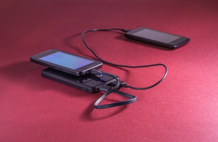 Two mobile phones are charging from powerbank. Red background. Small depth of field