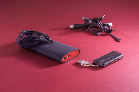 Cables, powerbank and USB hub are on red background. Small depth of field
