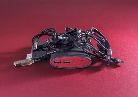 USB cables and powerbank are on red background. Small depth of field