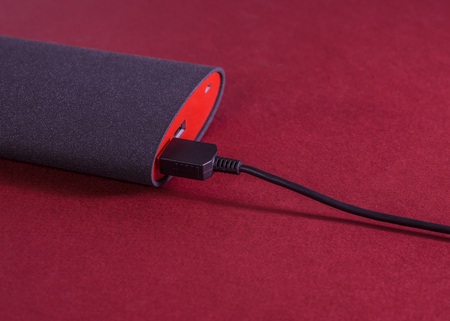 Cables from device is connected to powerbank. Red background. Small depth of field