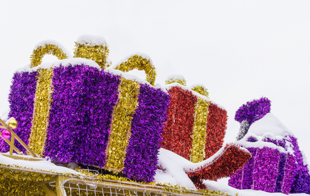 Christmas ornaments - gift boxes made from tinsel covered with snow are against cloudy sky. Copy space