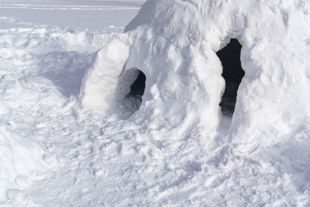 Snow house in shape of igloo. Winter kids amusement. Sunny day