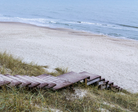 Wooden stairs down to sea from top of dune. Winter cloudy day