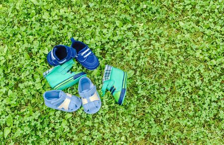 Three pairs baby shoes are on green lawn. View from above. Copy space