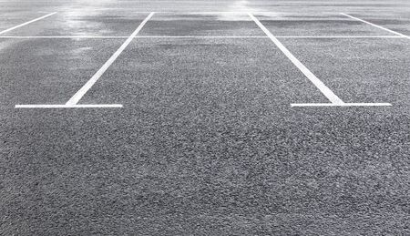 White marking lines of parking spots on wet asphalt surface of empty car park. Copy space Stockfoto
