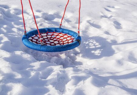 Rope swing of round shape is on winter playground. Winter sunny day. 版權商用圖片
