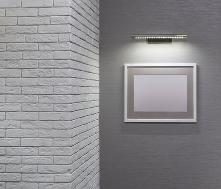 Empty picture frame hangs on wall under lamp of accent lighting next to brick wall. Copy space. Mockup