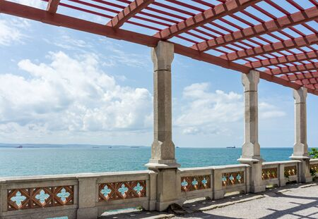 Pergola with stone pillars and fence is on promenade of resort against backdrop of sea landscape. Sunny day