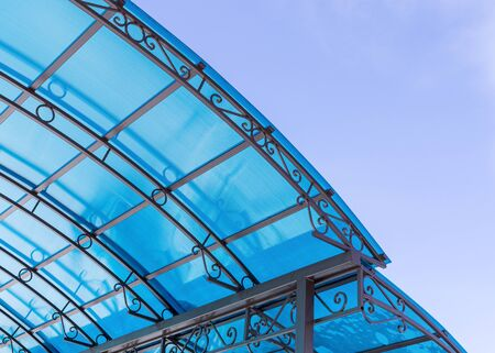 Fragment of pavilion roof made of polycarbonate against blue sky. Copy space