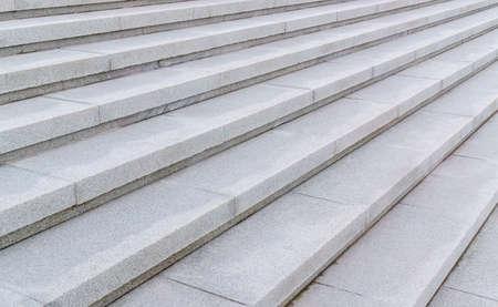 Steps of white granite staircase. Full frame