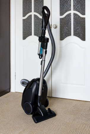 Vacuum cleaner with twister stands on carpet near door to room. Flexible hose and pipe with attachment for cleaning carpet and floor are fixed in upright position Standard-Bild