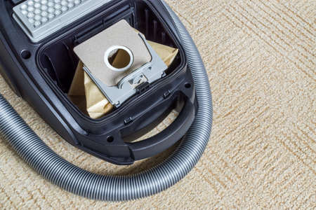 Paper bag for collecting dust is installed in vacuum cleaner with flexible hose. Top view. Copy space Standard-Bild