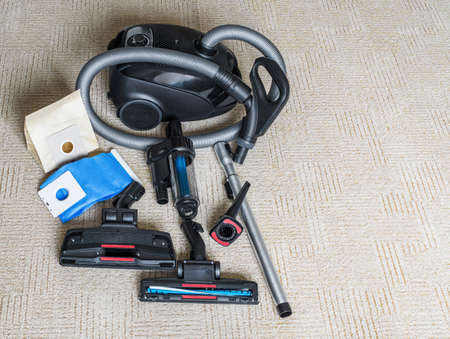 Vacuum cleaner with flexible hose and various attachments lie on carpet. Top view. Copy space