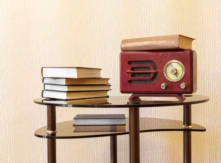 Wooden retro radio receiver and stack of books are on glass coffee table. Copy space