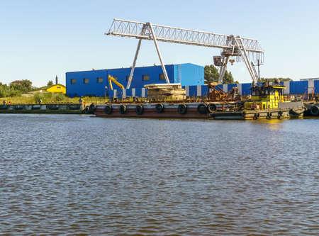 Overhead crane near logistics terminal of cargo port. Sunny day. Copy space