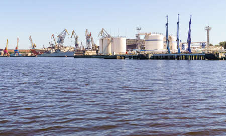 Wharf near tanks of oil loading or liquefied gas terminal in cargo port. Sunny day