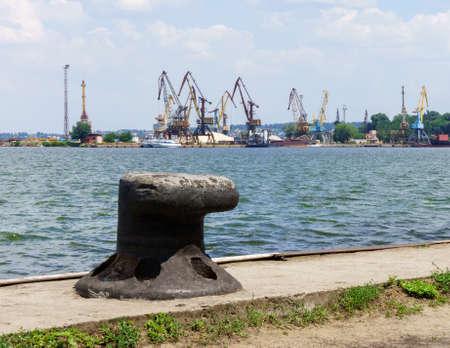 Iron bollard for mooring the ships is on wharf of cargo port. Summer sunny day Standard-Bild
