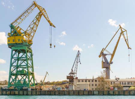Portal cranes are near dockside of cargo port. Sunny day