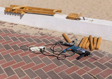Two electric drills, old hammer and wooden work pieces lie near sandy beach. Sunny day. Copy space Standard-Bild
