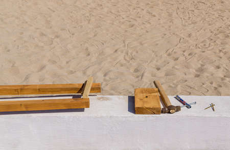 Old hammer, screws and wooden work pieces lie on the concrete parapet near sandy beach. Sunny day. Copy space