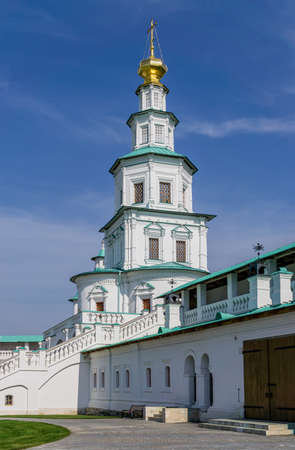 ISTRA, RUSSIA - SEPTEMBER 12, 2017: Steeple of multilevel church above entrance gate of orthodox New Jerusalem Monastery and stairs to gallery in wall. Sunny day Editorial
