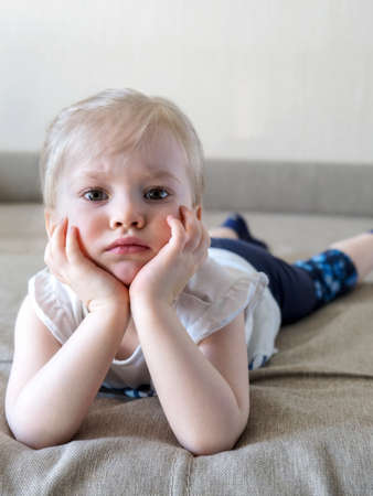 Pensive little girl with blonde hair is lying on couch with her face propped up in her hands. Looking at camera. Small depth of field Standard-Bild