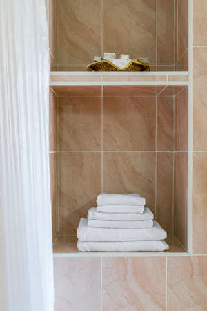 Stack of white terry towels and hygiene accessories are in alcove of wall. Fragment of bathroom interior