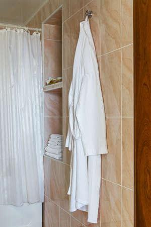 White bath robe is hanging on hook. Fragment of bathroom interior